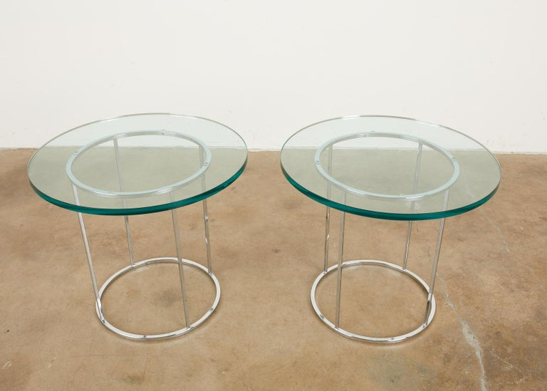 Stylish pair of mid-century modern chrome drinks tables attributed to Milo Baughman. The steel round frames feature Milo's iconic thin line profile design with a lovely chrome finish. Topped with thick round panes of glass. From an estate in
