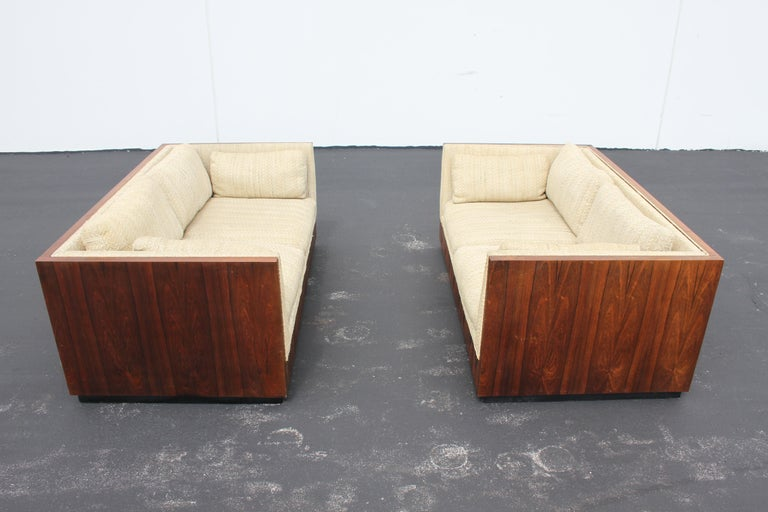 Pair of Milo Baughman for Thayer-Coggin model 1976 cubed formed settees with rosewood veneer on black floating base. Shown in all original condition with sun fading to finish, (Price includes refinishing of rosewood), work to be done prior to
