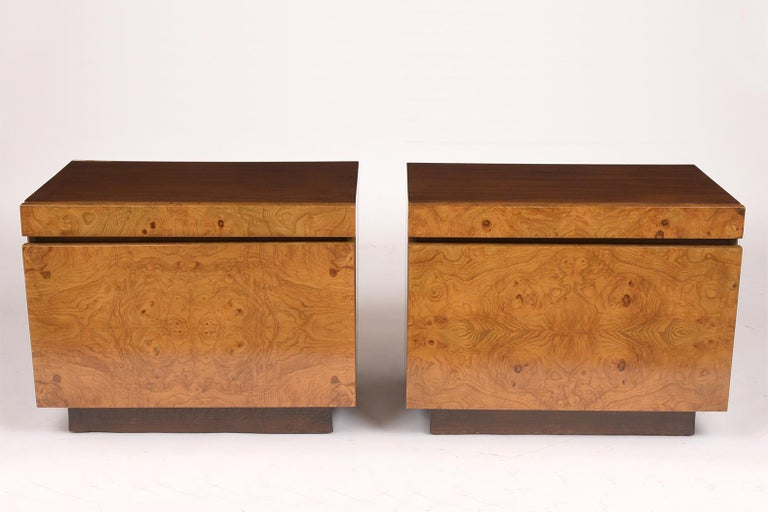 This pair of 1960s Burled Milo Baughman style nightstands are in great condition and feature a newly lacquered finish. The pair has a walnut colored frame and the two pull-outs are covered in a rich oak colored veneer. They also come with a pull-out