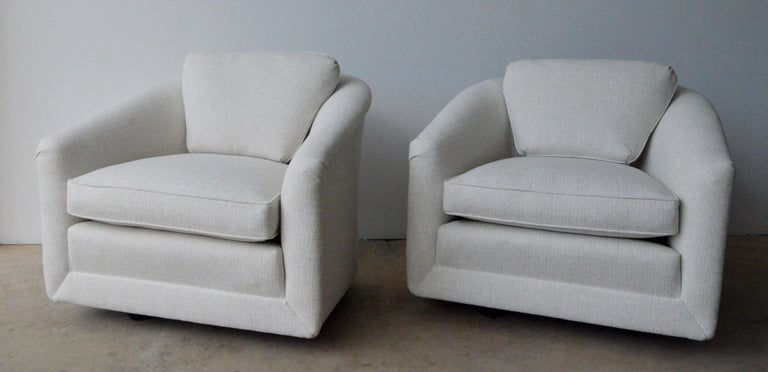 Offered is a pair of Mid-Century Modern Milo Baughman style swivel chairs with non-exposed wood base and back cushion in newly upholstered creamy white tweed. This pair of swivel chairs exudes luxury in style, material and color. The comfort and