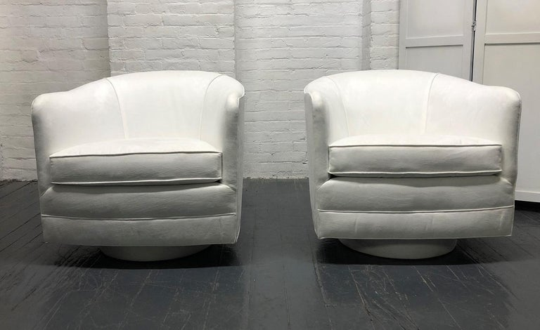 Pair of Milo Baughman style swivel lounge chairs. The chairs swivels 360 degrees. Beautiful pure white ultra suede upholstery.