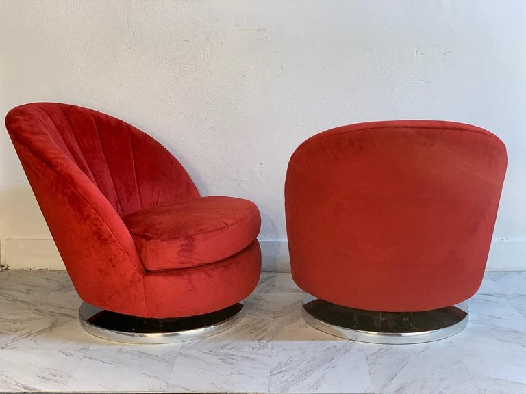 Pair of Milo Baughman swivel lounge chairs for Thayer Coggin. The chairs have circular chromed steel bases and upholstered in fuchsia-red velvet. Mid Century Modern.