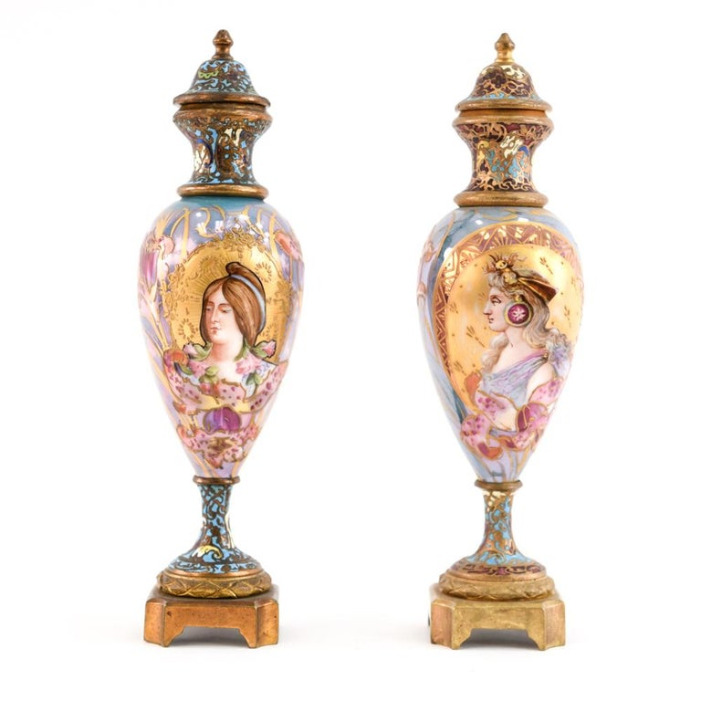 A wonderful combination of porcelain and champleve enamel work on the bronze these are a fantastic pair of mini urns that would draw attention to any shelf!