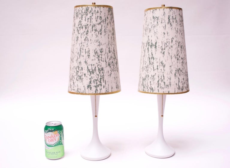 Pair of diminutive circa 1950s table lamps composed of simple, painted white wooden bases paired with off-white and green paper shades with gold trim. Lamps have been newly restored (socket and pull-chain are all new, as is the paint). The shades