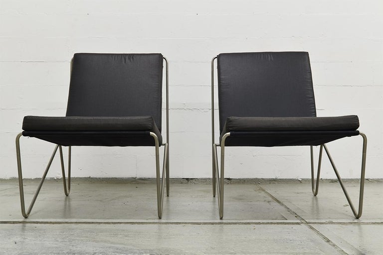 Pair of Minimalistic black Bachelor chairs designed by Verner Panton for the Danish company Fritz Hansen. Produced, circa 1960s. The frame is made of tubular steel and mounted with black canvas and the loose seat and back cushions were reupholstered