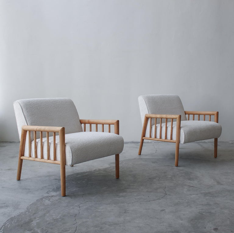 This is an absolutely gorgeous pair of midcentury lounge chairs designed by Leslie Diamond for Conant Ball. Absolutely gorgeous lines, constructed of solid wood that has been left au naturel, combined with an off-white, bouclé style fabric this is a