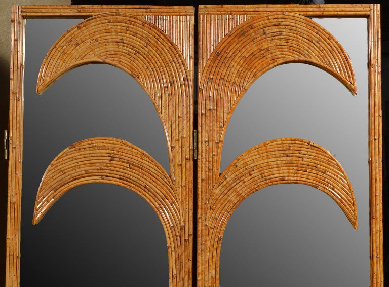 This pair of bamboo or rattan inlaid mirrored folding screens from Vivai del Sud's Parma series feature art deco stylized palm trees. The pair of panels can be used separately or as a four-panel screen. The panels a well constructed consisting of a