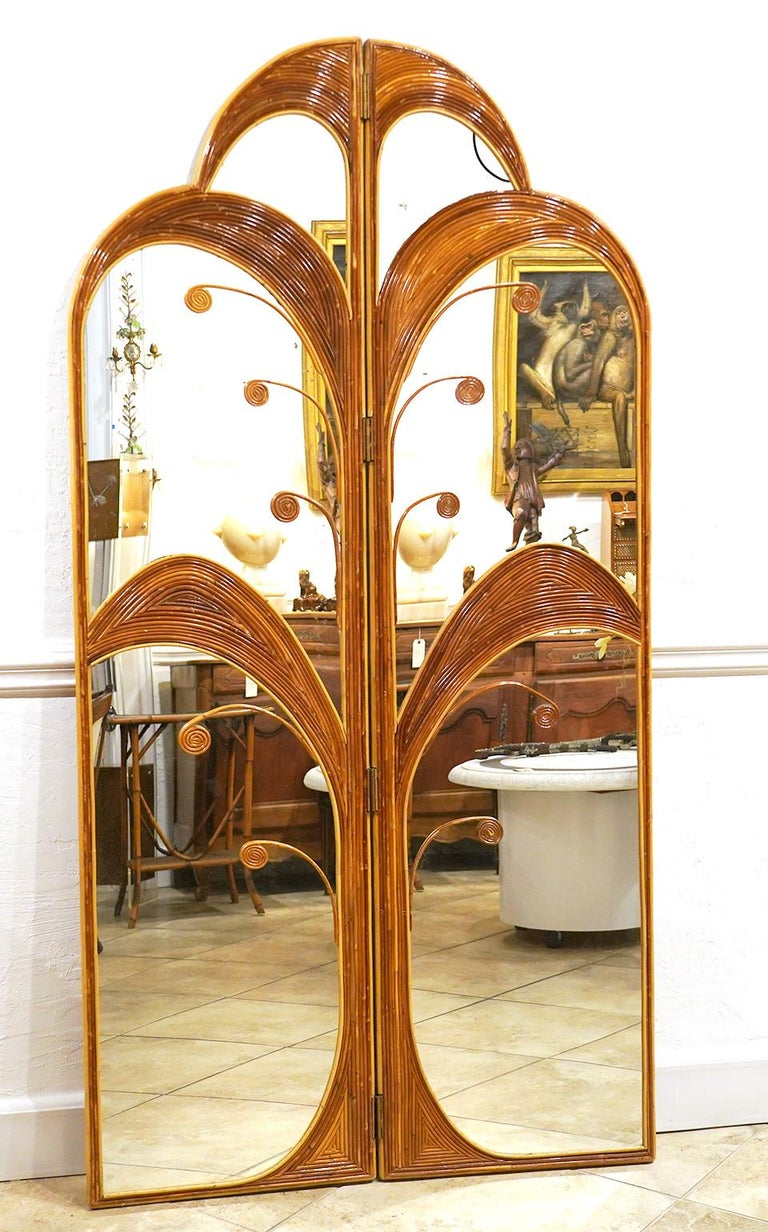 This pair of bamboo or rattan inlaid mirrored folding screens in the style of Vival del Sud feature art deco stylized palm trees hinged and with arched tops framing mirrors from top to bottom. The pair of panels can be used separately or as a