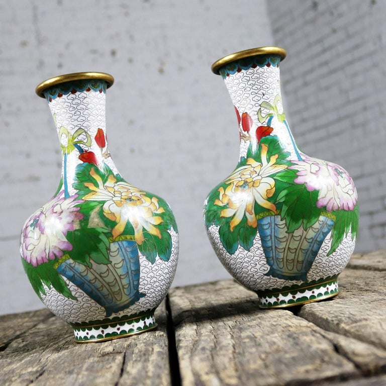 Beautiful pair of 20th century vases in white with multicolored floral and butterfly mirrored design. This pair is in fabulous vintage condition, circa 1960s-1980s