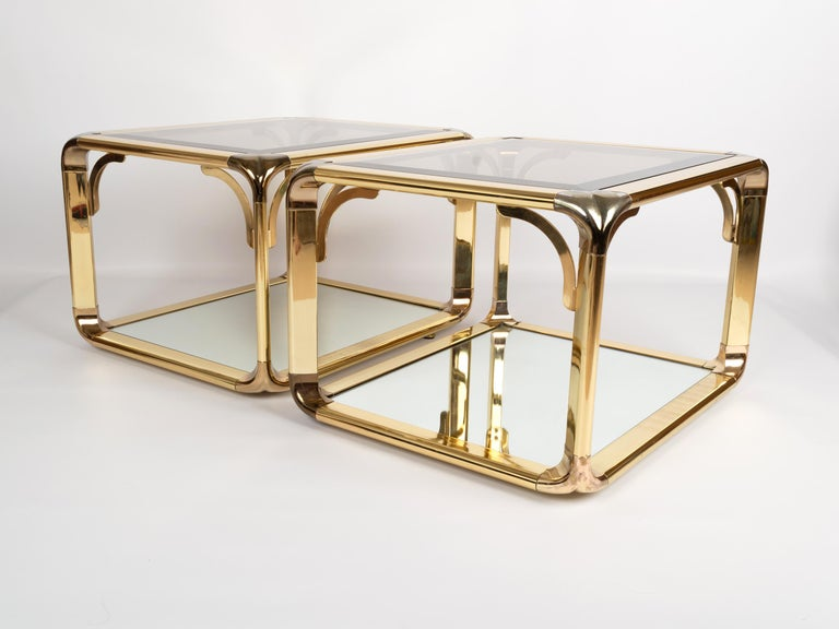 Pair of mirrored gold chrome two-tier end tables by Belgo Chrome, Belgium, circa 1970. Smoked glass top with a mirrored lower tier. In excellent vintage condition commensurate of age.