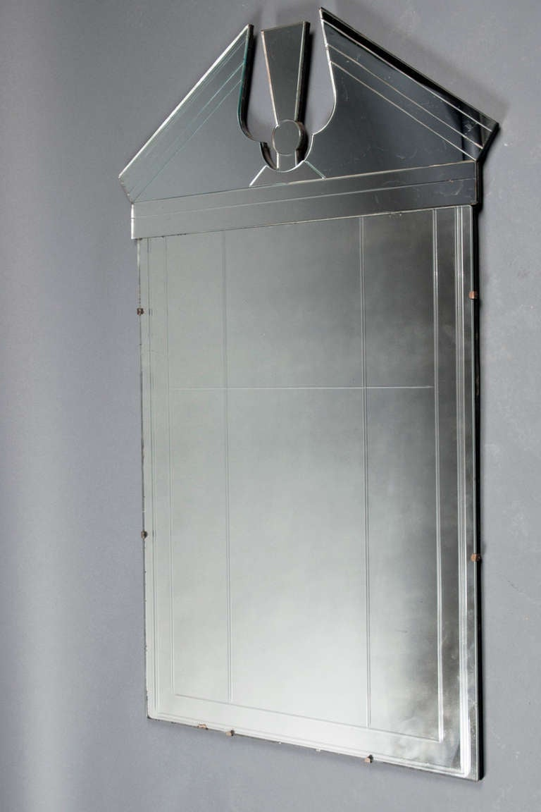 Mirrored glass with an arched top, framed in brass and mirrored tinted glass border. Mirror panels include age marks throughout.