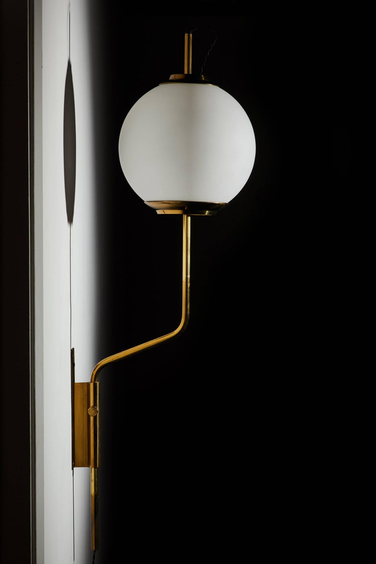 Pair of original model Lp11 pallone wall lights designed by Luigi Caccia Dominioni for Azucena. Manufactured in Italy 1958. Patinated brass and brushed sating glass with vertical positioning that pivots left/right. Original backplates. Wired in