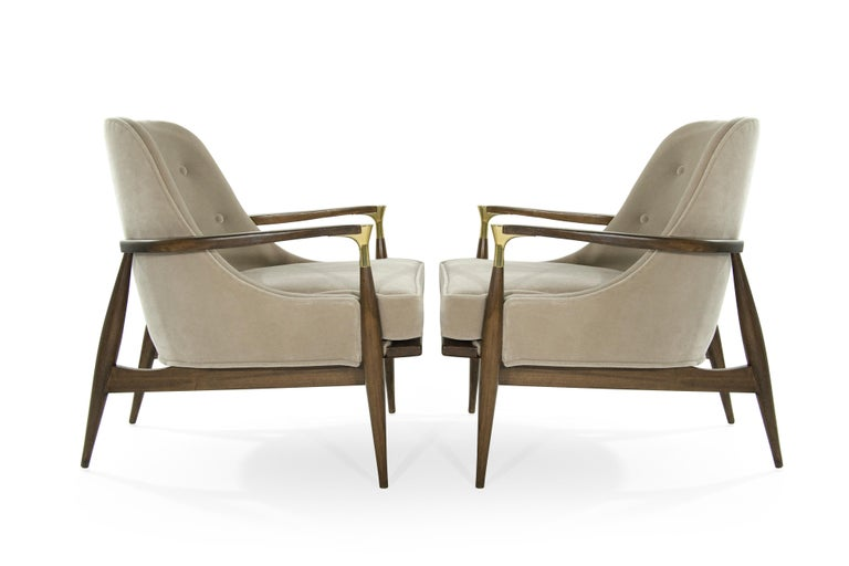Rare lounge pair of chairs in the style of Ib Kofod-Larsen. Featuring brass details on arms. Newly upholstered in natural mohair. Sculptural walnut frames completely restored.