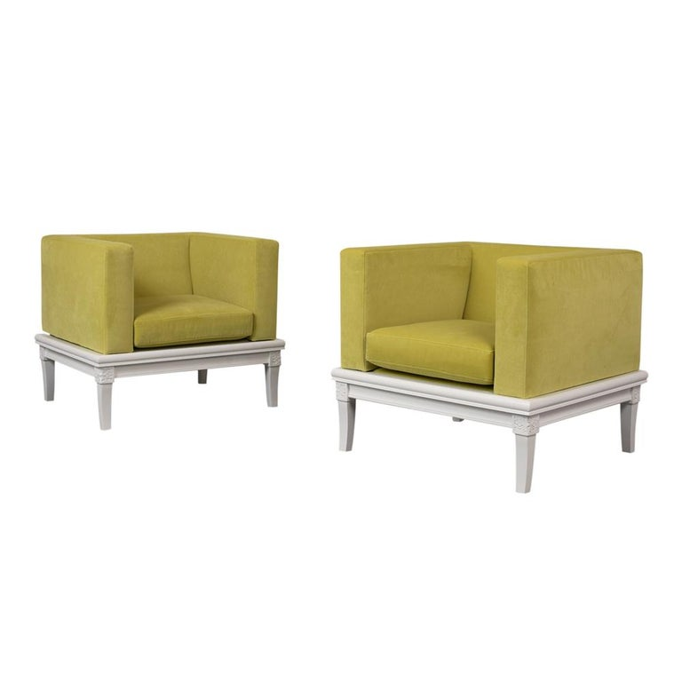 The pair of modern lowback cube lounge chairs features a wooden frame newly stained an elegant white color with a lacquered finish. The armrests and seat cushions are upholstered in a lemon green color velvet fabric with topstitch detail. These