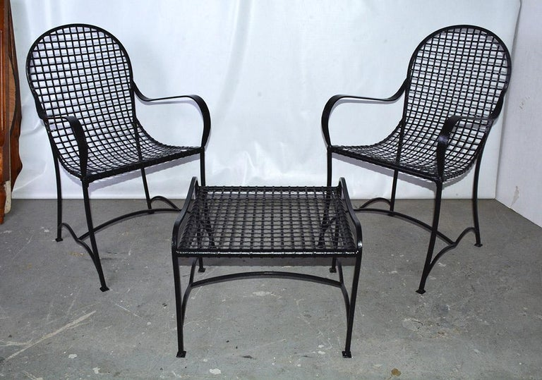 The pair of outdoor lounge chairs and coffee table, made of strips of open-weave black wrought iron. Decoratively curved stretchers secure the curved legs on all the pieces. The curve of the back to the seat adds overall comfort. Each chair