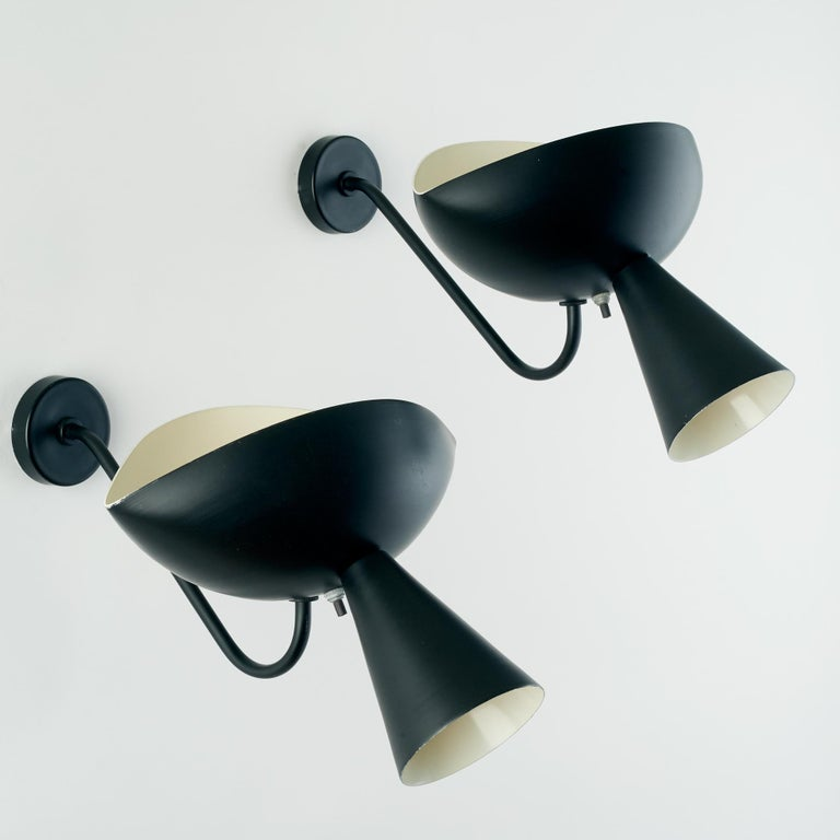 Serge Mouille (1922–1988)  Graceful and harmonious pair of Cachan model sconces in black and white enameled aluminum designed by Serge Mouille in 1957 and produced later. The arms have been replaced.  France, second half of the 20th century.   11