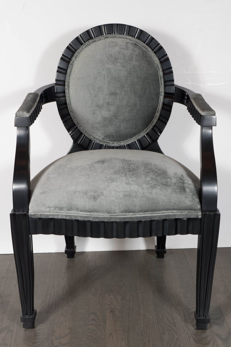 This stunning pair of modernist chairs were realized by the esteemed designer Donghia in the United States, circa 1980. They feature ebonized walnut bodies with circular backs, conical legs and scalloped channel detailing that runs around the border