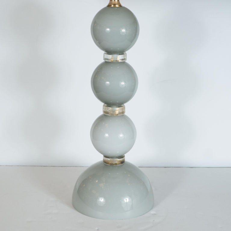 This elegant pair of table lamps were hand blown in Murano, Italy- the islands off the coast of Venice centuries renowned for superlative glass production. Each lamp has three vertically stacked, identical dove grey colored glass spheres which rest
