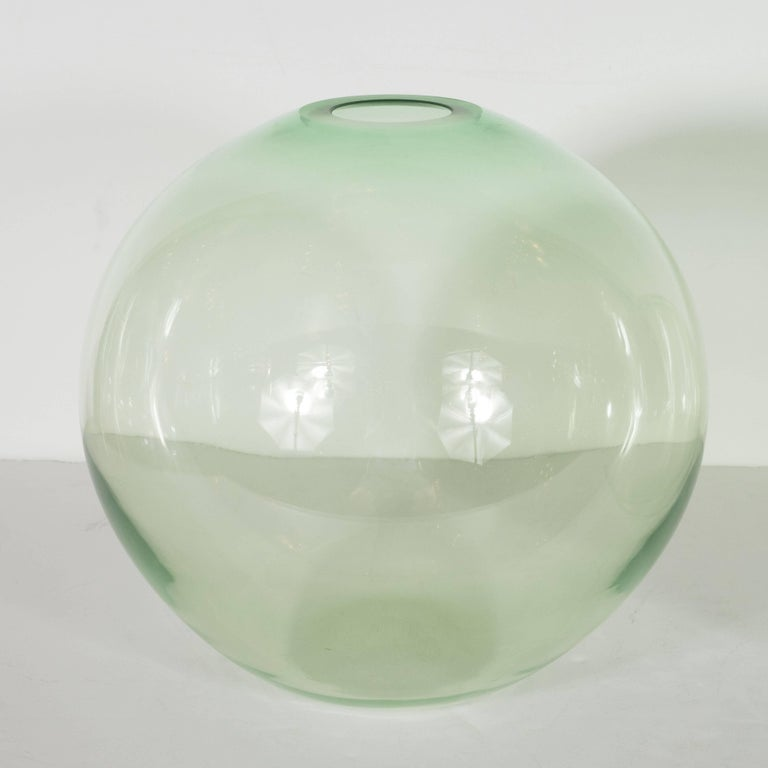 This pair of globular vases have been hand blown by the esteemed Brooklyn based artist Nick Leonoff in an emerald hue of translucent glass. With their radiant palate and organic forms, they are perfect as functional vases for presenting flowers, and
