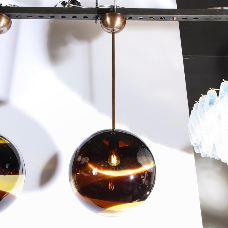 This elegant pair of modernist pendants were handblown in Murano, Italy- the island off the coast of Venice renowned for centuries for its superlative glass production. The fixtures offer spherical bodies in smoked amber Murano glass with undulating
