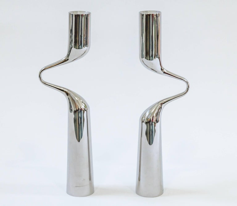 Striking pair of mirror finish steel candleholders from the Mikaela Dorfel studio. Modernist and harmonious. Inspired by dance and movement. When placed together they resemble a dancing embrace. Striking pair for your tabletop.