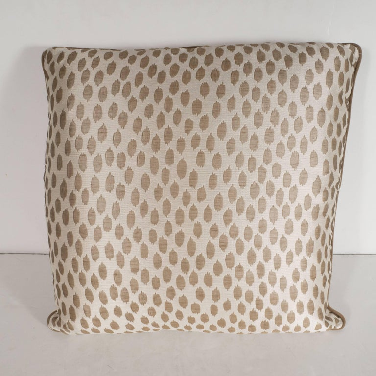 This elegant pair of square modernist pillows features organic forms in muted gold hue- with piping in a matching tone- that float against an ecru background with a horizontal weave. With its austere form and sophisticated fabric, this pillow would