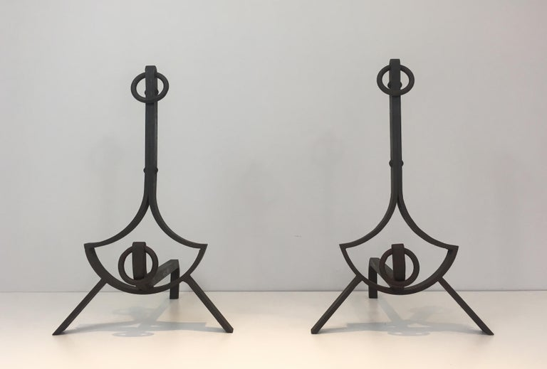 This pair of modernist wrought iron andirons have pure lines and are very elegant. Very nice quality with rivets. French work, circa 1940.