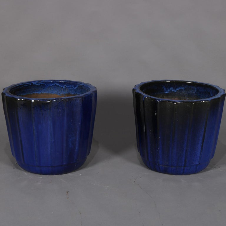 Pair of monumental jardinière garden urns feature terra cotta pottery construction with flared and ribbed form having cobalt blue glazing, signed on base as photographed, 20th century.  ***DELIVERY NOTICE – Due to COVID-19 we are employing