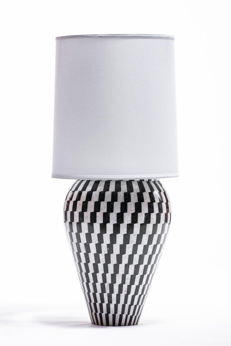Pair of large scale Kelly Wearstler tessellated marble and onyx geometric urn shaped lamps. Black and white geometric tiles of marble and onyx cover the neoclassical forms. Dramatic and chic, elegant but playful. These lamps were custom designed for