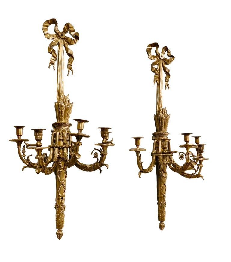 Rare Pair of French Neoclassical style gold bronze and brass quiver of arrows 5-light candelabra sconces. Extra-large one-of-a-kind intricately detailed gold bronze shaft in the shape of quiver of arrows hung by a grand neoclassical ribbon motif;