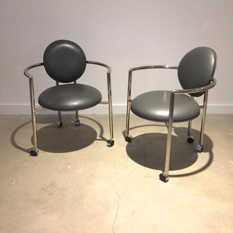 Pair of Moon chairs designed in 1986 by Stanley Jay Friedman for Brueton. Roundabout frame of mirror polished tubular No. 304 stainless steel arm chairs in the Memphis style. Seat and back upholstered in gray leather. 24