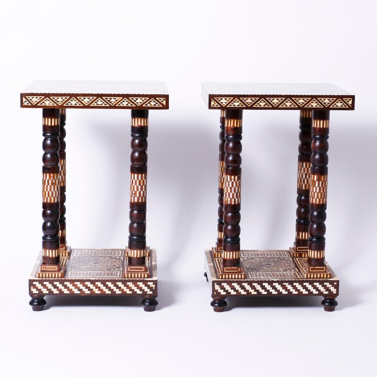 Pair of Moroccan tables or stands with square tops decorated with inlaid mother of pearl, tortoise, bone and exotic hardwoods, supported by four turned and inlaid columns on an inlaid base with turned feet.
