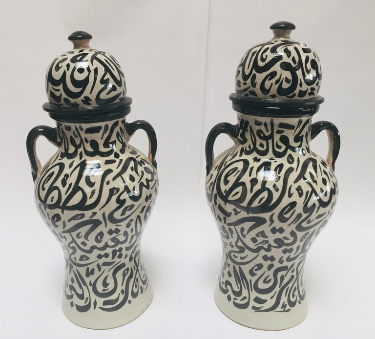Pair of Moroccan glazed ceramic urns from Fez. Moorish style ceramics handcrafted and hand painted in Fez with Arabic calligraphy writing design in black on ivory background. This kind of Art Writing looks calligraphic is called Lettrism, it is a