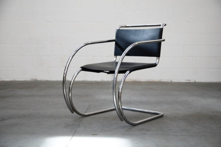 An incredible set of two (2) signed cantilevered MR 20 armchairs by Ludwig Mies van der Rohe for Knoll. In excellent showroom condition, this collectible pair of arm chairs possess their original Knoll Made in Italy labels. The black saddle leather