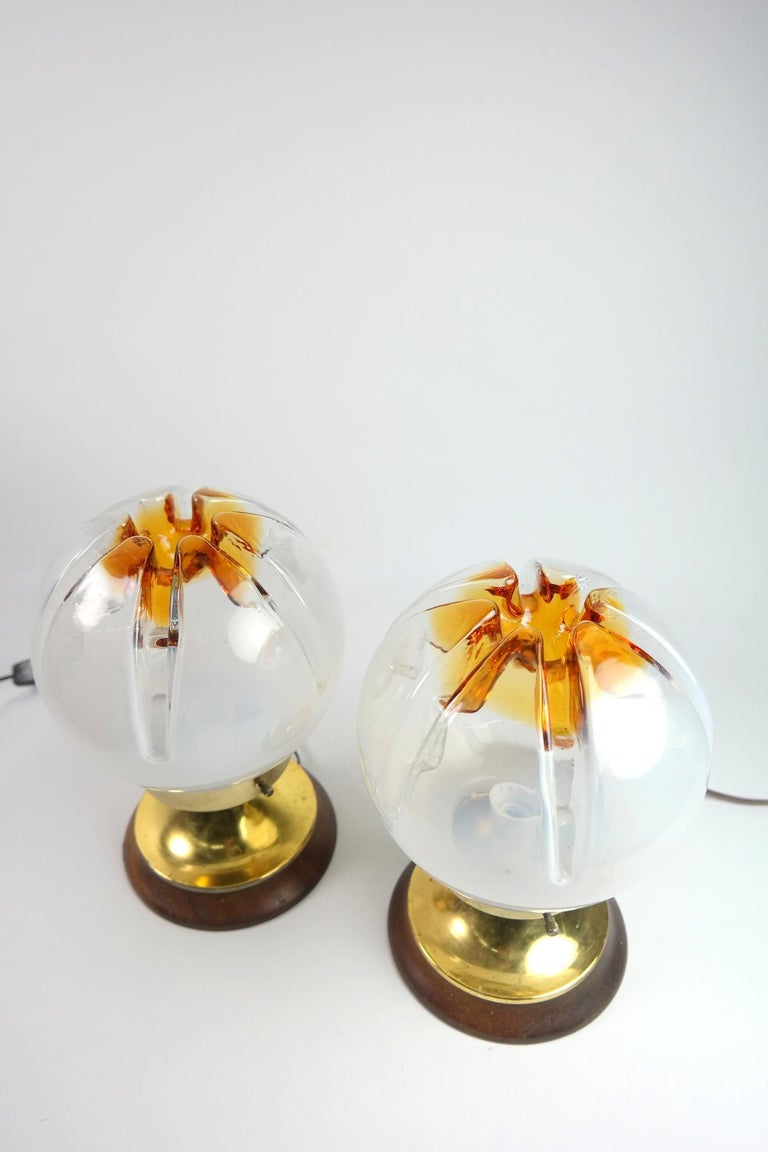 This pair of Murano glass and wood table lamp feature a brass base and was made by Mazzega, Murano, 1970s. It's in good condition.