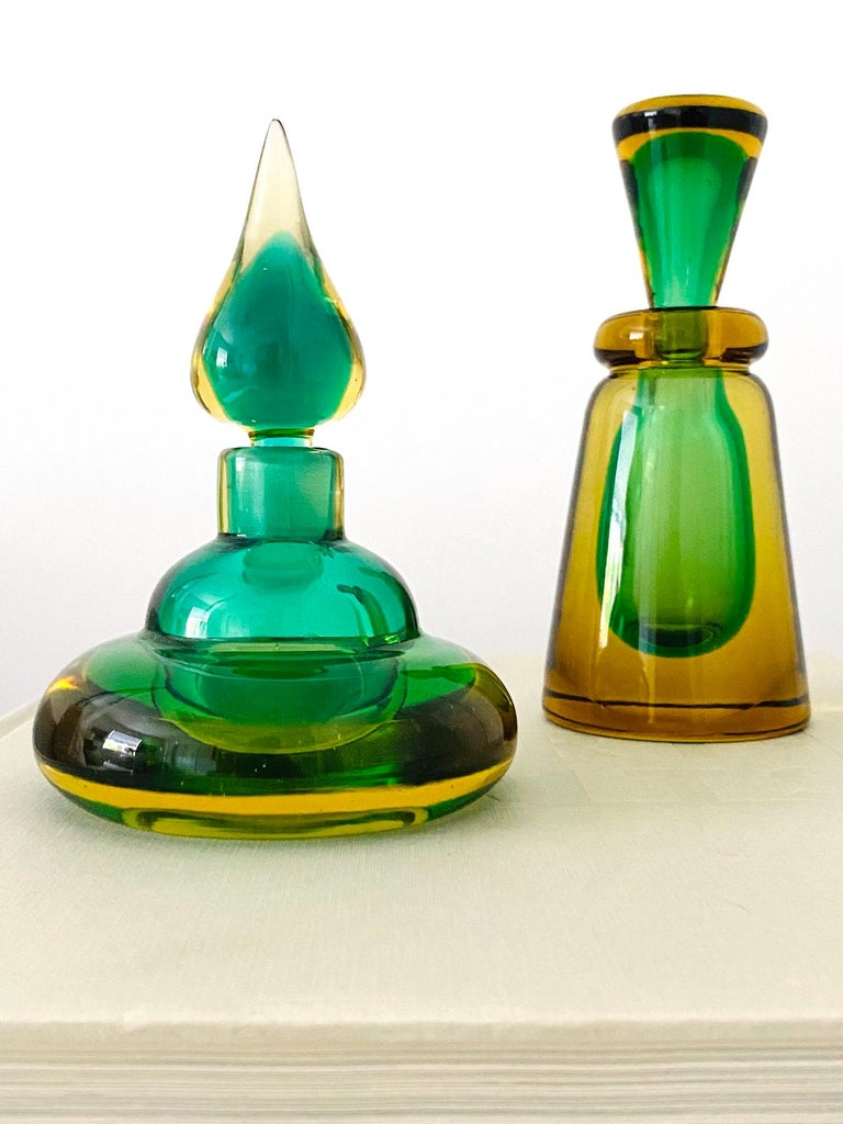 Mid-Century Modern decorative bottles or vintage perfume bottles by Flavio Poli for Seguso. Beautifully handcrafted in vibrant hues of emerald green and golden yellow. Hand blown glass with Sommerso technique. One features a stylized genie bottle