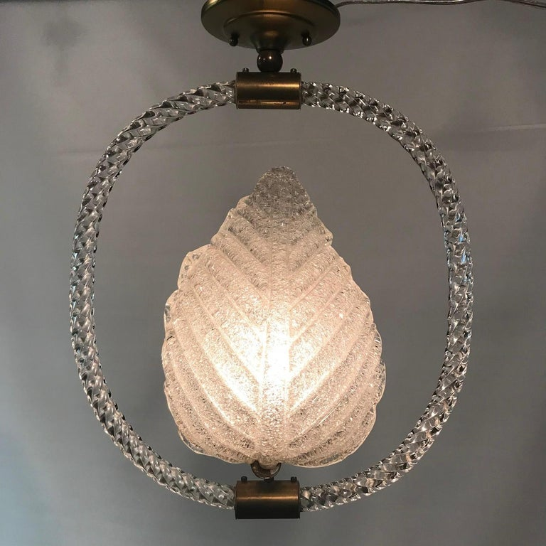 Pair of Moderne aventurine glass Murano leaf-form hanging fixtures each suspended in twisted glass rope circle by a brass shank, designed by Ercole Barovier for Barovier and Toso.