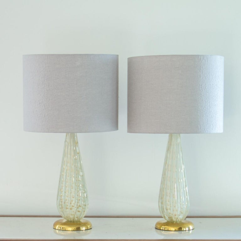 A pair of tapered Murano white glass lamps which have been ribbed and blown with gold bubble details throughout. The lamps are set on brass bases, 1960s.   There is an old repair to the back of the lamp.   Base diameter is 16cms.