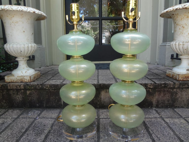 Fabulous pair of midcentury Murano glass lamps in celadon green or sea foam green with gold inclusions. These stunning Hollywood Regency Murano glass stacked ball or stacked sphere lamps are comprised of 4 large glass spheres and brass accents