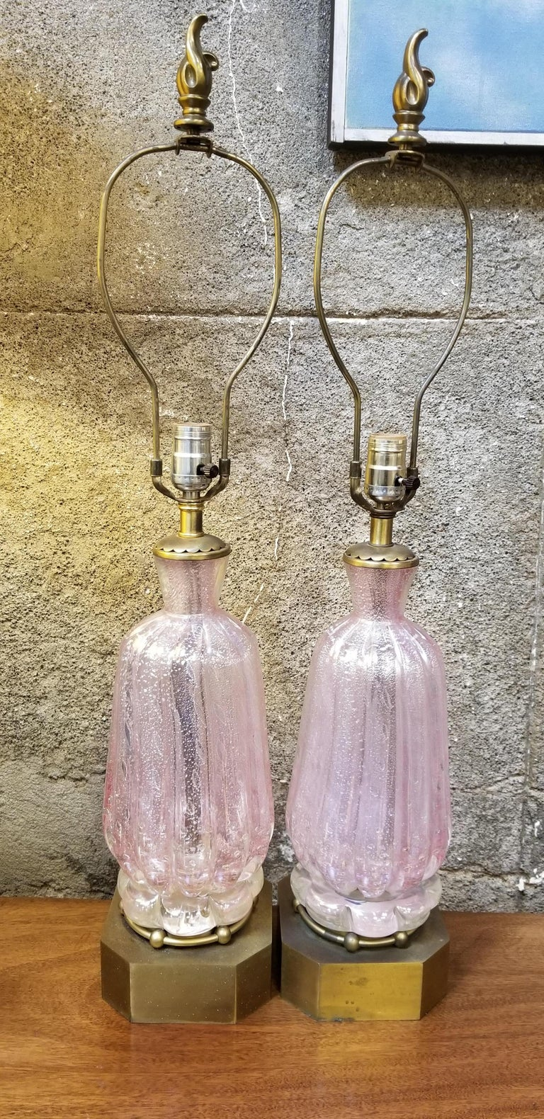 A pair of hand blown Murano glass table lamps, pink bubble glass with floating silver leaf detail. Original, vintage condition. Original brass bases. Original harps and flame brass finials, circa 1960s. No shades. Glass only measures 13.25 inches in