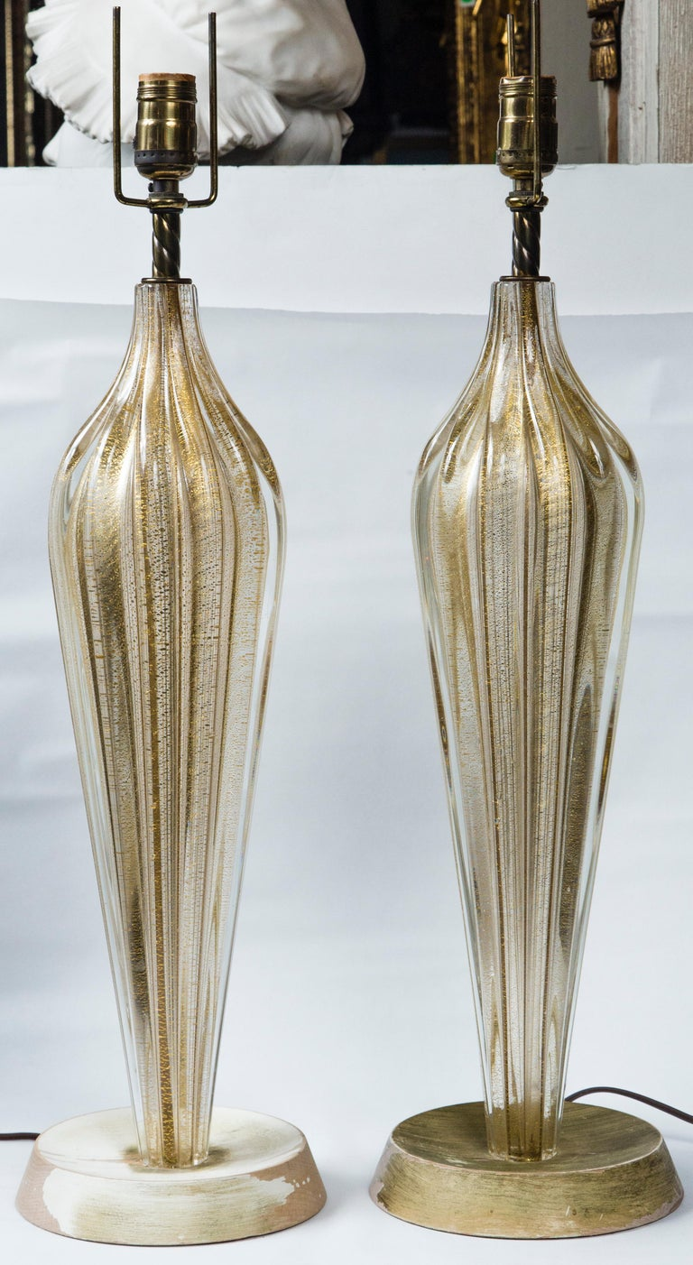 Of gold and clear thick glass in long inverted teardrop shape, ribbed. The gold appears to be gold colored