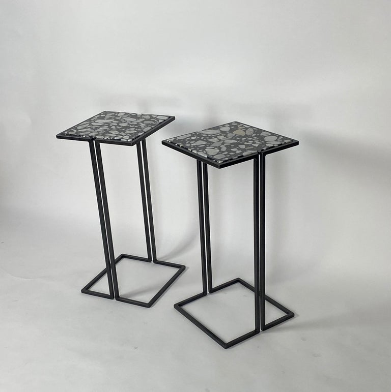 Two small-scale side tables. Minimalist design with gun metal patina frames and Palladrio Moro marble tops. Versatile tables, perfect for cocktails, laptops. These side tables nestle nicely around the arms of chairs to provide a nice sized