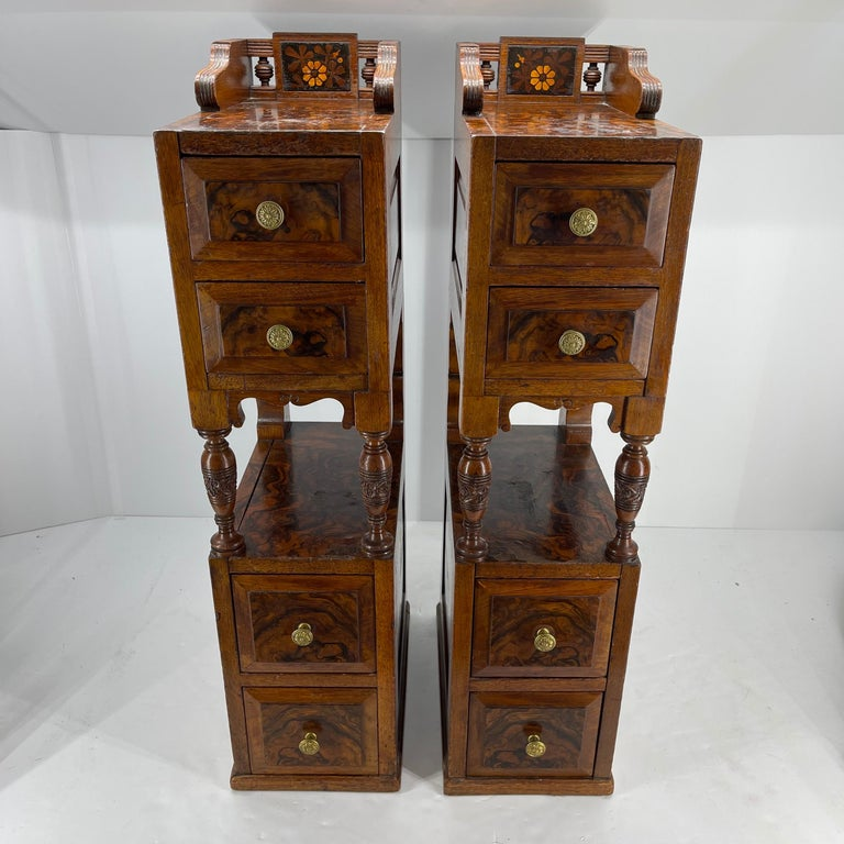 Pair of narrow nightstands with amazing bird's-eye maple veneer inlay. The stands each have 4 drawers with the original brass hardware. The stands can also be used as end tables or side tables.