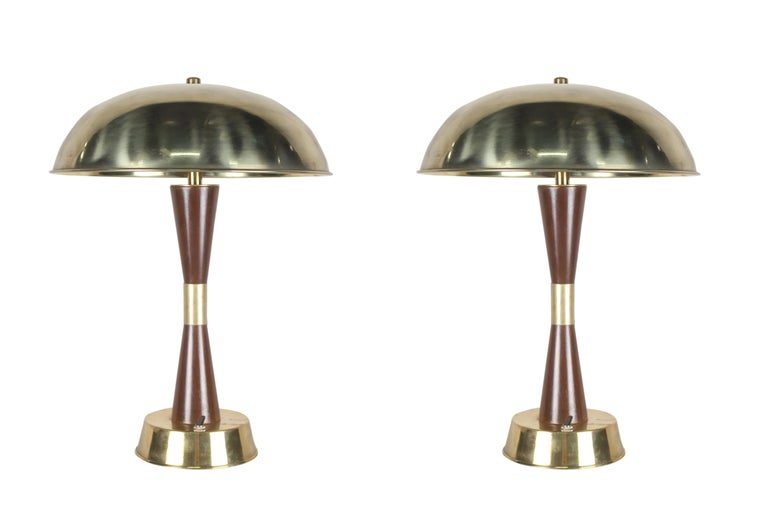 A handsome pair of teak and brass table lamps from the stateroom of a decommissioned cruise ship. 1980's. On/off switch at base. Rewired for American use. Base diameter is 6