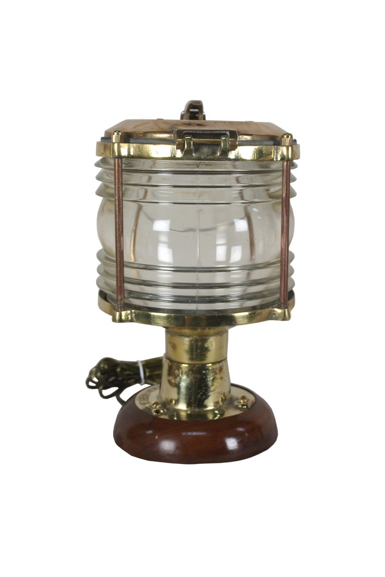 A pair of handsome brass ship's post lights with Fresnel Lens glass. These have been mounted on a teak base to use as table lamps. Rewired for American use and take a standard base light bulb. The brass top has a latch that lifts for access, 1970s,