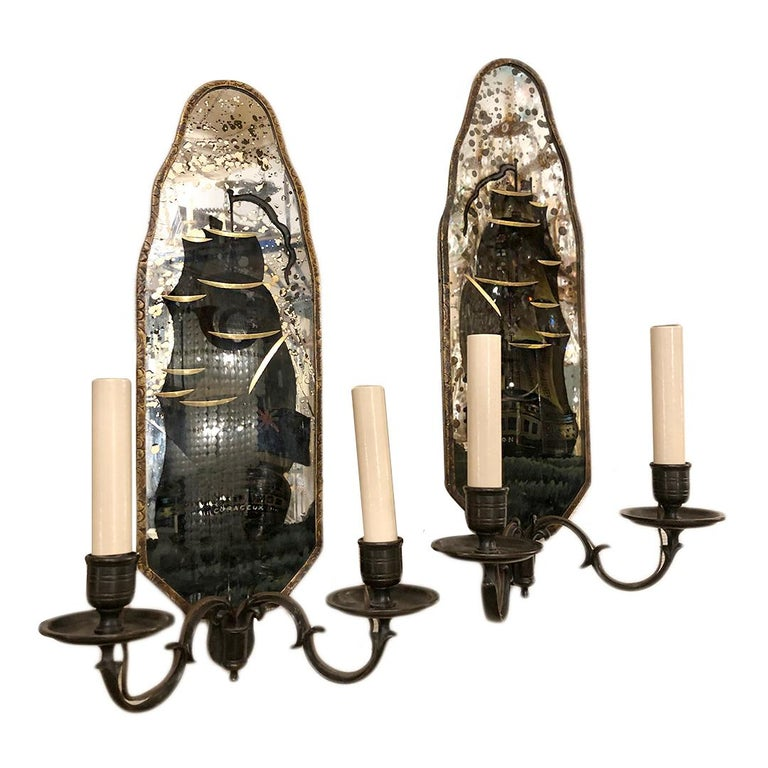 1920's American Caldwell mirrored sconces with etched and reverse painted ships.  Measurements: Height: 17″ wide: 5.5″ Depth: 5.5″