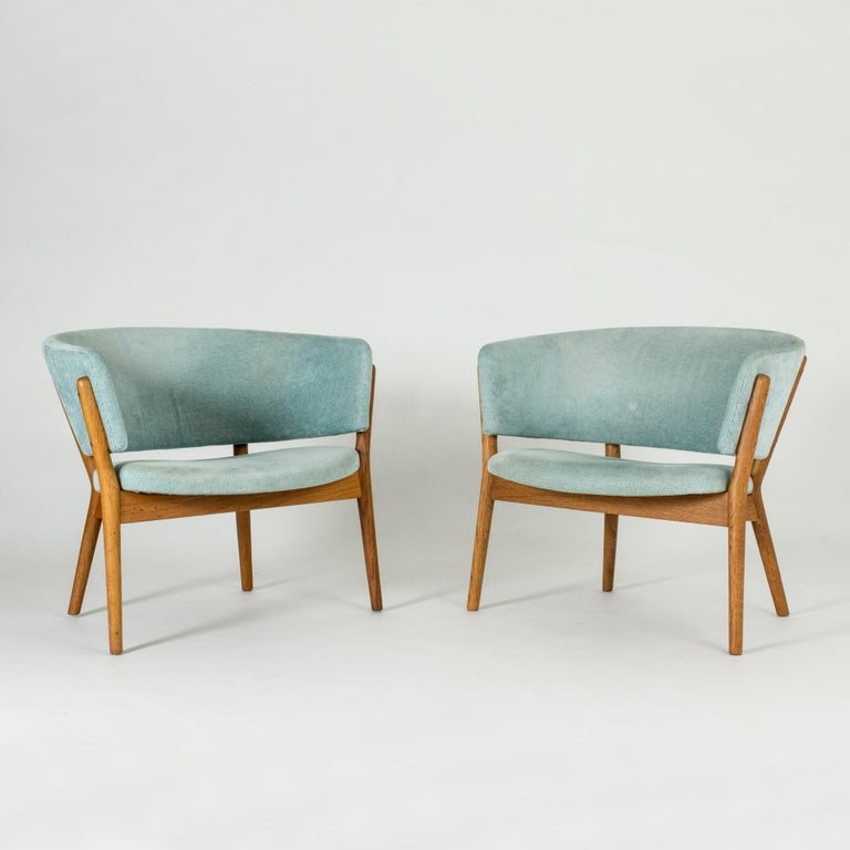 "Pair of beautiful ""ND 83"" lounge chairs by Nanna Ditzel, designed in 1952. Frames made of solid oak, upholstered with a cool aquamarine colored vintage fabric. The elegant simplicity and inviting design are characteristic of Nanna Ditzel's style."