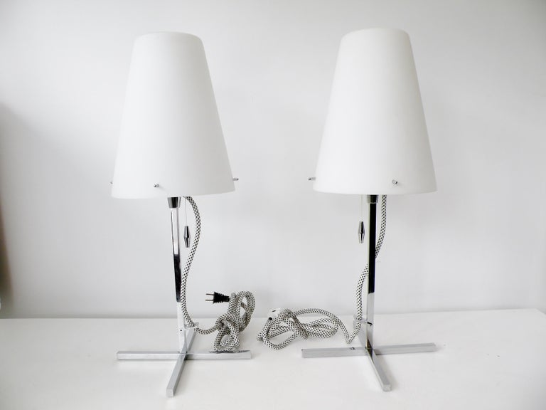 Pair of Nemo Thuban Tavolo table lamps designed by Hannes Wettstein. Bodies of polished chrome steel with clean Italian modernist lines, satin white blown glass diffuser shades, and white/ black fabric covered cords with in line dimmers.