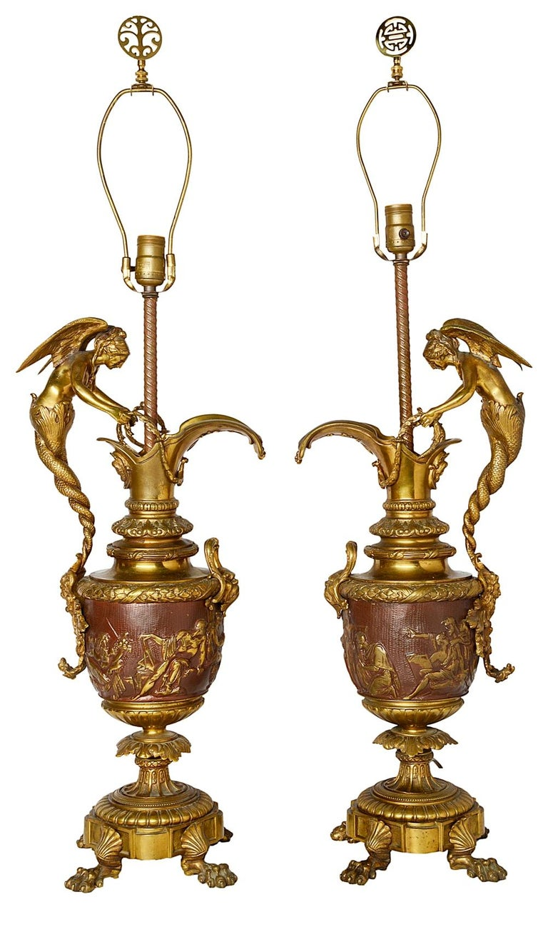 A good quality pair of late 19th century neoclassical bronze and ormolu ewer lamps. Each with wonderful winged mermaid like handles, mythical masks and classical scenes to the central panel, raised on foliate and shell decorated bases with claw feet.