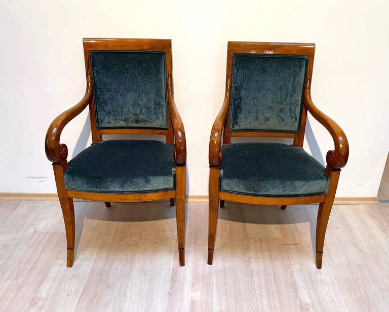Very elegant pair of restored neoclassical Biedermeier / Restoration Armchairs from France, circa 1830.  Solid walnut wood, shellac hand-polished (Frenhc Polish). Very elegantly curved armrests with attached rosettes/rosaces. Newly upholstered
